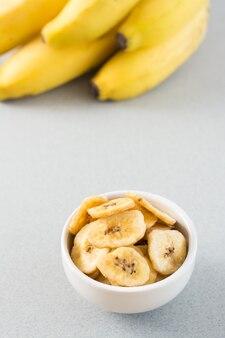 Pieczone chipsy bananowe w białej misce i kilka bananów na stole. fast food. skopiuj miejsce. widok pionowy