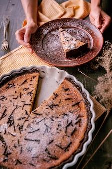 Pieczone ciasto w formie ceramicznej posypane kawałkami czekolady na drewnianym stole. kromka ciasta ułożona na glinianym talerzu i ozdobiona kwiatkiem. płyta trzymająca ręce kobiet