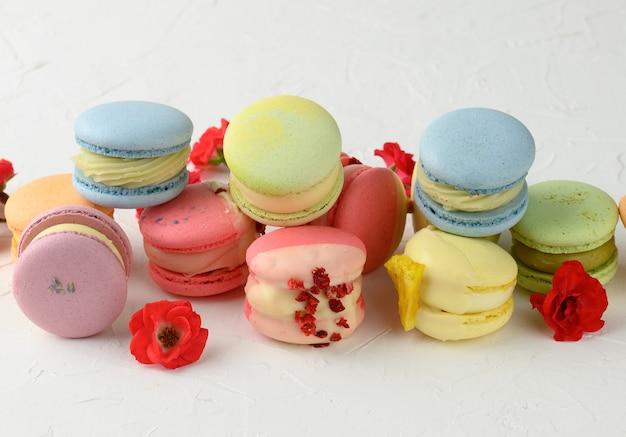 Pieczone czerwone makaroniki i czerwone pączki róż na białym stole, wyśmienity deser z mąki migdałowej, widok z góry