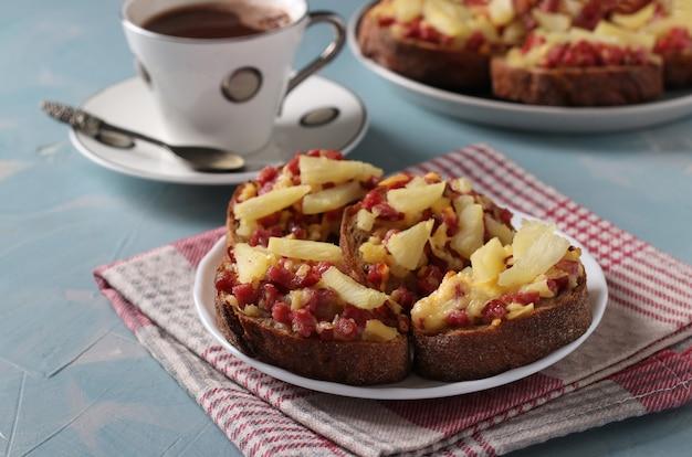 Pieczone domowe kanapki na ciepło z kiełbasą, serem i ananasem. pyszne śniadanie lub przekąska. zbliżenie