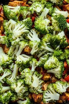 Pieczone filety z kurczaka mięso z warzywami korzeniowymi na patelni. ciemne tło widok z góry