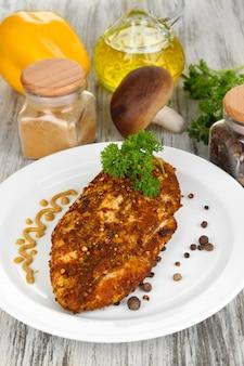 Pieczone filety z kurczaka na białym talerzu i warzywa na drewnianym stole