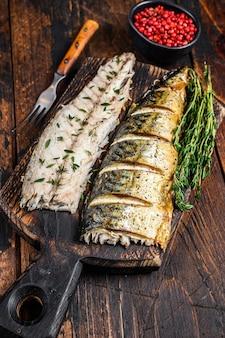 Pieczone filety z makreli na desce do krojenia.
