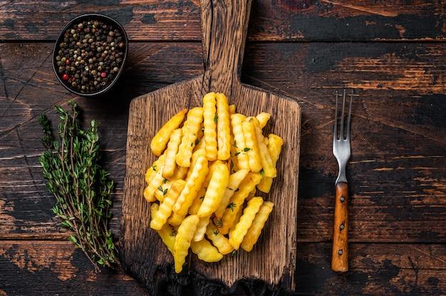Pieczone frytki marszczone paluszki lub frytki na drewnianej desce.