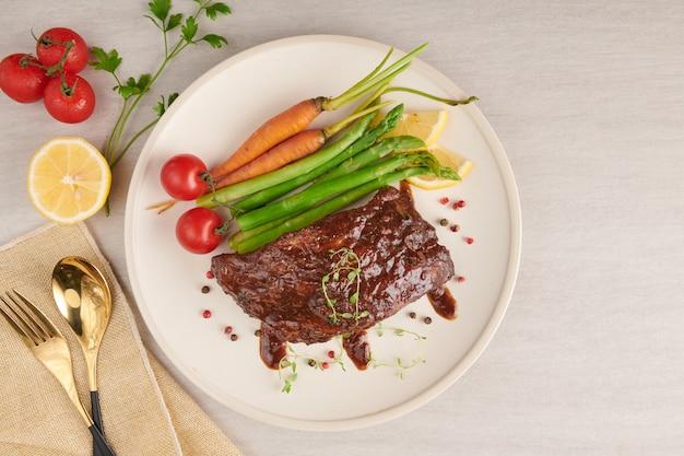 Pieczone, grillowane żeberka wieprzowe z letniego grilla podawane z warzywami, szparagami, młodą marchewką, świeżymi pomidorami i przyprawami. wędzone żeberka w białym talerzu na kamiennej powierzchni. widok z góry.