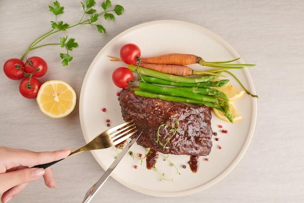 Pieczone, grillowane żeberka wieprzowe z letniego grilla podawane z warzywami, szparagami, młodą marchewką, świeżymi pomidorami, przyprawami na białym talerzu. kobieta ręce z widelcem i nożem, jedzenie żeber. widok z góry.