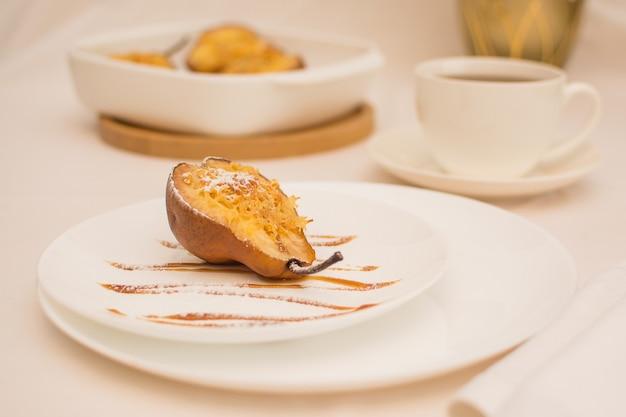 Pieczone gruszki z orzechami i serem na białym talerzu ceramicznym z karmelem.