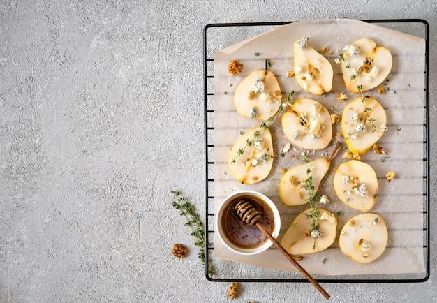 Pieczone gruszki z serem pleśniowym, orzechami włoskimi, miodem i ziołami.