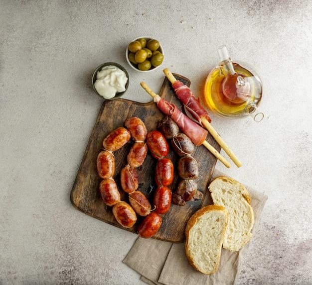 Pieczone hiszpańskie kiełbaski na desce do krojenia - butifarra blanca, chorizo, morcilla de cebolla, jamon i czosnek sause aioli