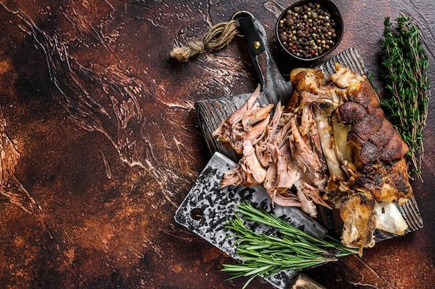 Pieczone i krojone niemieckie mięso z golonki wieprzowej na drewnianej desce z tasakiem do mięsa