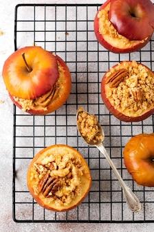 Pieczone jabłka nadziewane orzechami pekan, cynamonem, streyzel i miodem na starym jasnym tle betonu. rustykalny nieświeży