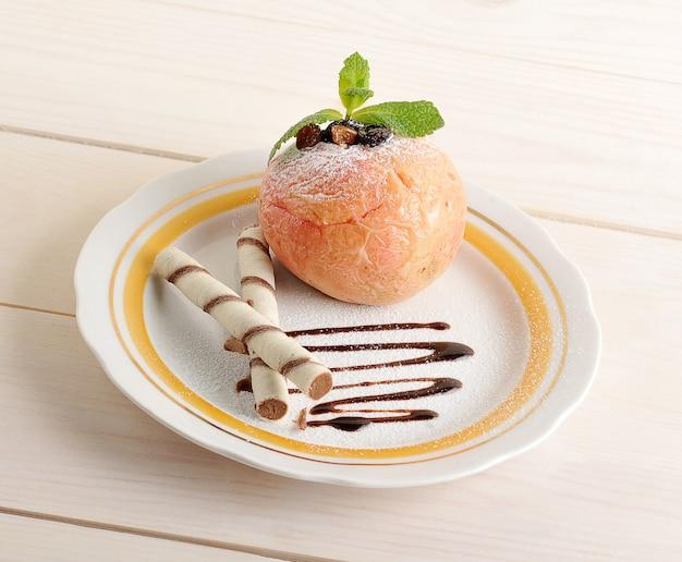 Pieczone jabłko z rolkami waflowymi na talerzu z czekoladą i cukrem pudrem