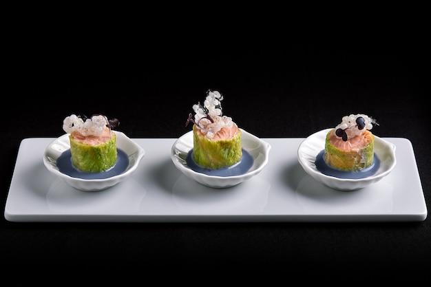 Pieczone kanapki z łososiem z sosem, w białych małych spodeczkach, jedzenie koncepcyjne.