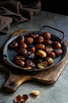 Pieczone kasztany, smażone na szarym ciemnym tle, gotowe do spożycia, kopiować miejsca