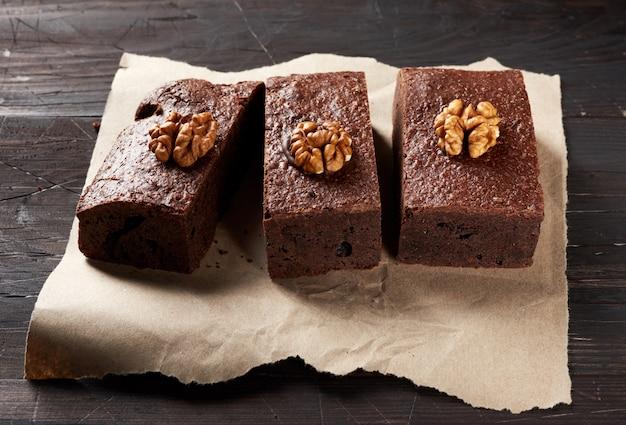 Pieczone kawałki ciasta czekoladowego brownie z orzechami na brązowej kartce papieru, widok z góry, pyszny deser