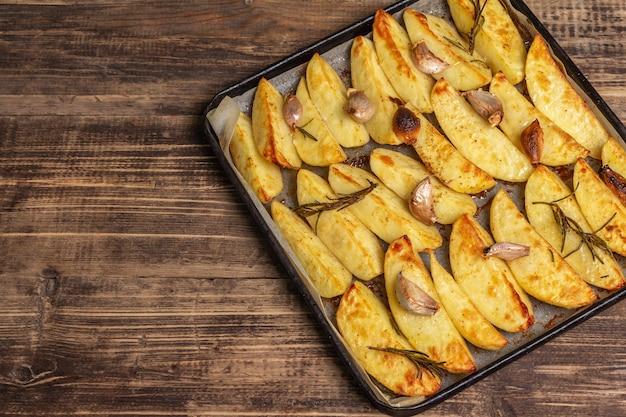 Pieczone kawałki pikantnego ziemniaka na blasze do pieczenia
