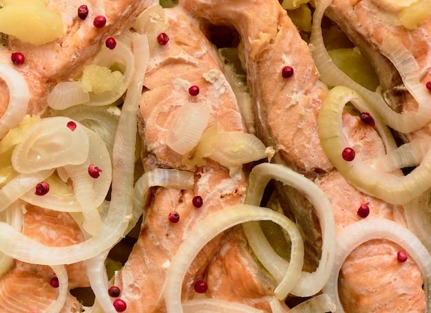Pieczone kawałki pstrąga z cebulą, ziemniakami i różową papryką, tło