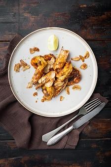 Pieczone krewetki tygrysie z chutneyem z mango i chrupiącym czosnkiem, na talerzu, na starym ciemnym drewnianym stole