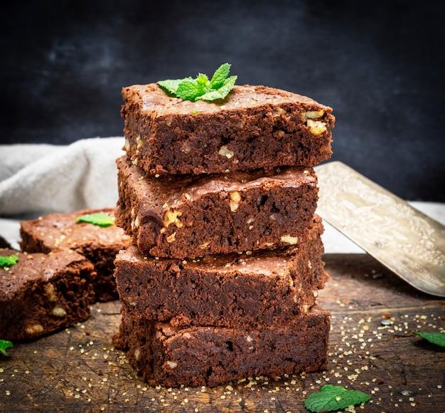 Pieczone kwadratowe kawałki ciasta czekoladowego brownie z orzechami