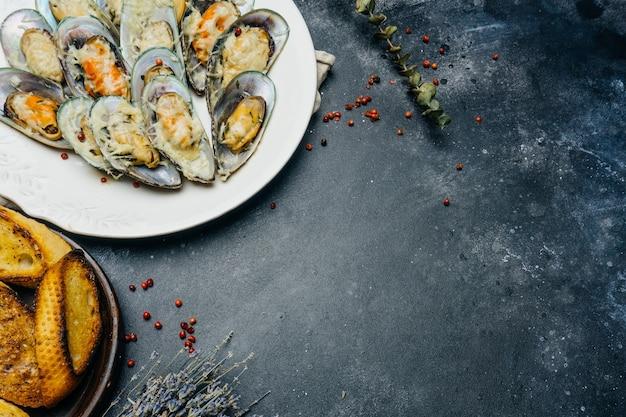 Pieczone małże zielone z parmezanem i grzankami czosnkowymi na białym talerzu