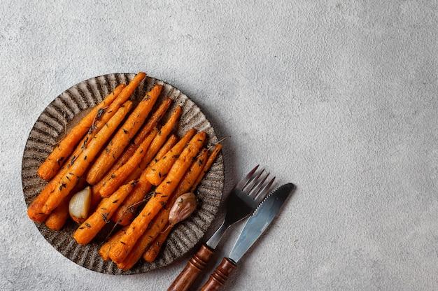 Pieczone marchewki gotowe do spożycia. glazurowana marchewka z ziołami i czosnkiem. smażone marchewki na białym tle. smażone warzywa. komfortowe jedzenie. świąteczne dekoracje