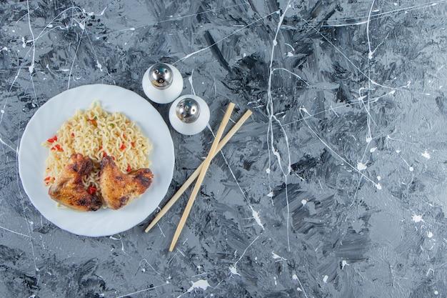 Pieczone mięso i makaron na talerzu obok soli i pałeczek, na marmurowym tle.