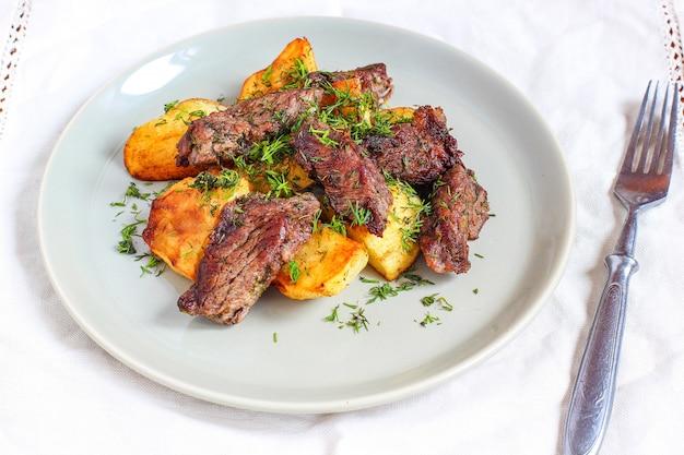 Pieczone mięso i smażone ziemniaki z sosem keczup i majonezem