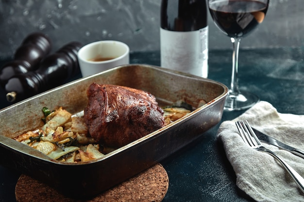 Pieczone mięso i ziemniaki. pyszny i obfity posiłek. duży upieczony kawałek mięsa. gotowane gorące jedzenie.
