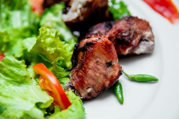 Pieczone mięso na białym talerzu.
