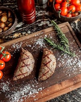 Pieczone mięso w formie ciast z przyprawami na drewnianej desce