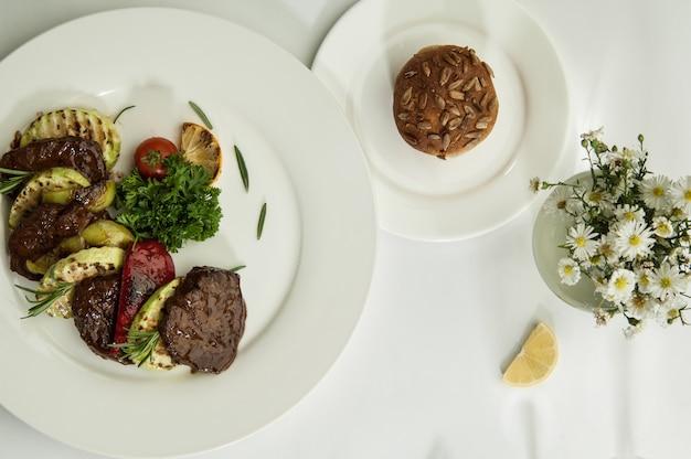 Pieczone mięso z plasterkami cytryny na białej powierzchni z cieniem z kieliszków do wina