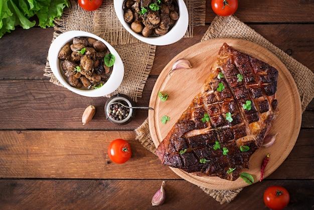 Pieczone mięso z przyprawami i czosnkiem na drewnianym stole. widok z góry