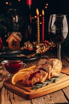Pieczone mięso z sosem borówkowym i lampką wina na świątecznym stole.