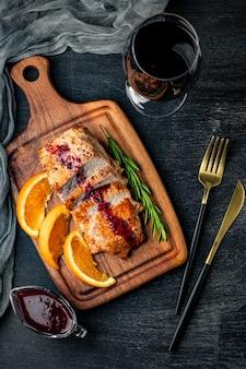Pieczone mięso z sosem borówkowym i lampką wina, widok z góry.