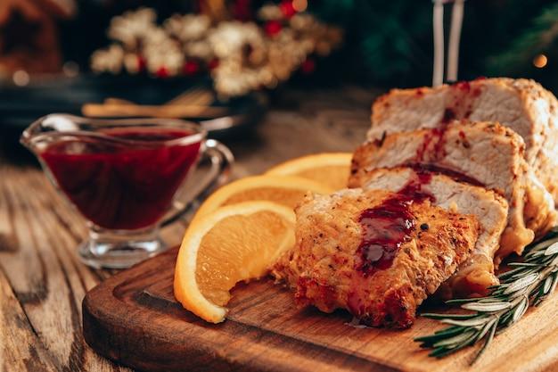 Pieczone mięso z sosem borówkowym i pomarańczami na świątecznym stole.