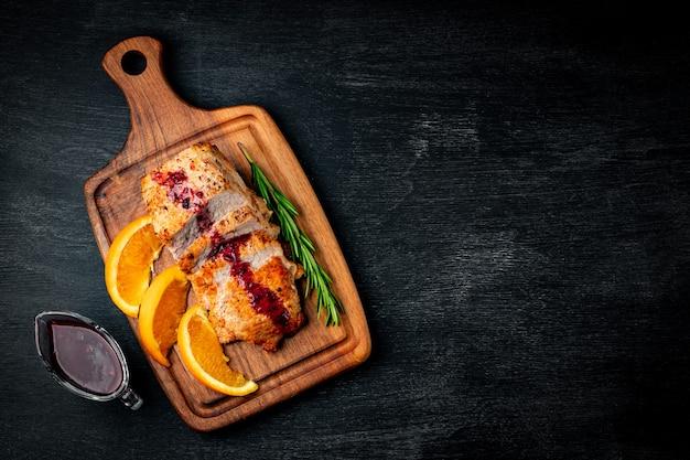 Pieczone mięso z sosem borówkowym na czarnym tle