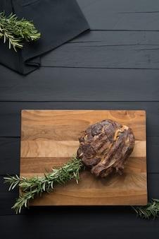Pieczone mięso z zieleniną na desce do krojenia na czarnym drewnianym tle