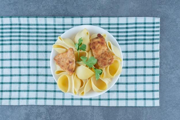 Pieczone nuggetsy z kurczaka i gotowany makaron w białej misce.