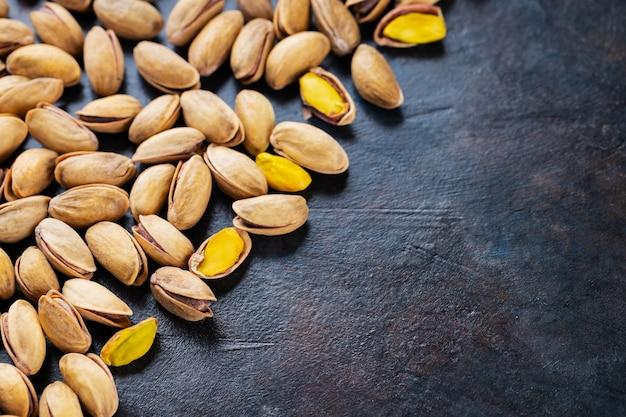 Pieczone orzeszki pistacjowe na ciemnym tle. pistacje - zdrowe wegetariańskie pożywne białko. zdrowa przekąska. skopiuj miejsce. widok z góry