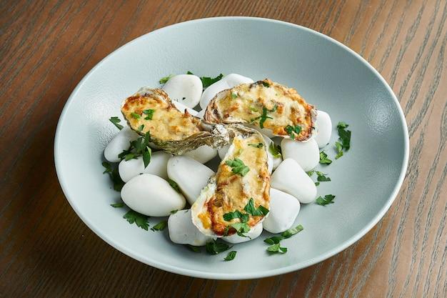 Pieczone ostrygi z serem na morzu, gorące kamienie na drewnianej powierzchni. zdrowe owoce morza. efekt filmowy podczas postu. nieostrość