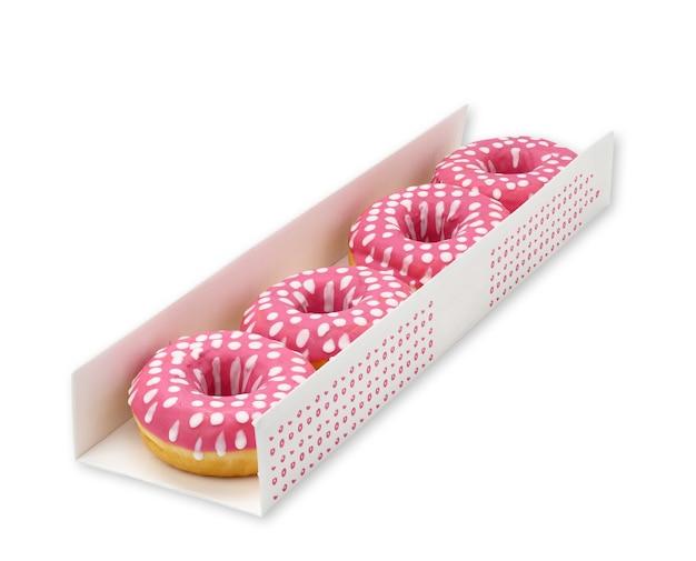 Pieczone pączki z różowym lukrem w białym kartonowym pudełku na białym tle