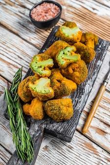 Pieczone panierowane brokuły na drewnianej desce z ziołami