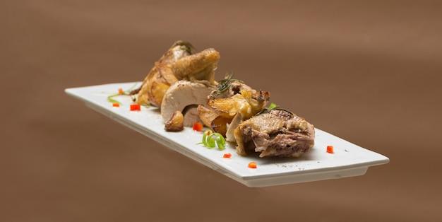 Pieczone perliczki z ziemniakami, z zielonymi ziołami, umieszczone na białym talerzu, brązowym tle