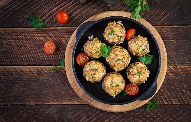 Pieczone pieczarki faszerowane mięsem mielonym z kurczaka, serem i ziołami na drewnianej powierzchni