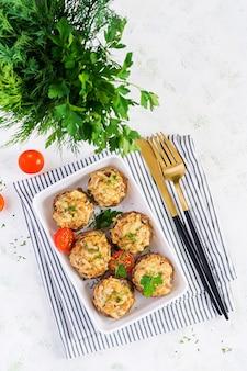 Pieczone pieczarki faszerowane mięsem mielonym z kurczaka, serem i ziołami na jasnym talerzu