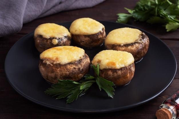 Pieczone pieczarki faszerowane serem i ziołami na czarnym talerzu. drewniane tła.