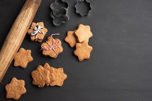 Pieczone pierniki w kształcie gwiazdy, drewniany wałek do ciasta i metalowe foremki na czarnym stole, widok z góry