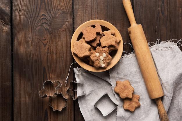 Pieczone pierniki w kształcie gwiazdy, drewniany wałek do ciasta i metalowe foremki na drewnianym stole, widok z góry