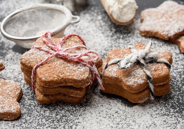 Pieczone pierniki w kształcie gwiazdy posypane cukrem pudrem na czarnym stole, z bliska