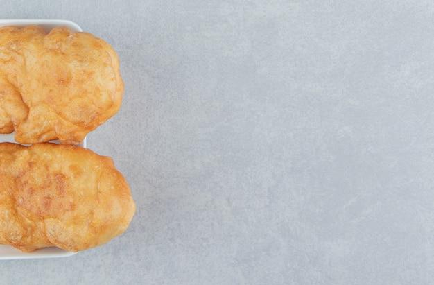 Pieczone piroshki z ziemniakami w białej misce.